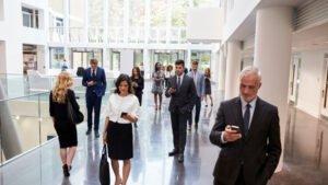 photo of people walking in large office workspace looking at their smartphones